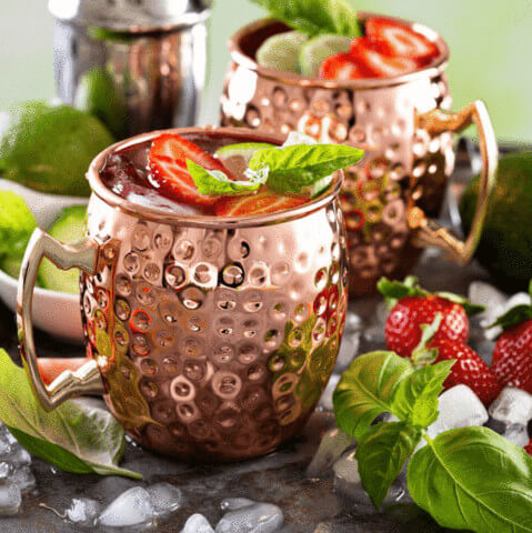 two Moscow Muled copper mugs filled with liquid strawberry ice and mint leaves