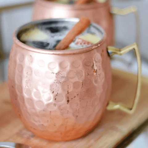 Moscow Muled copper mug filled with liquid ice and sliced lime on its rim