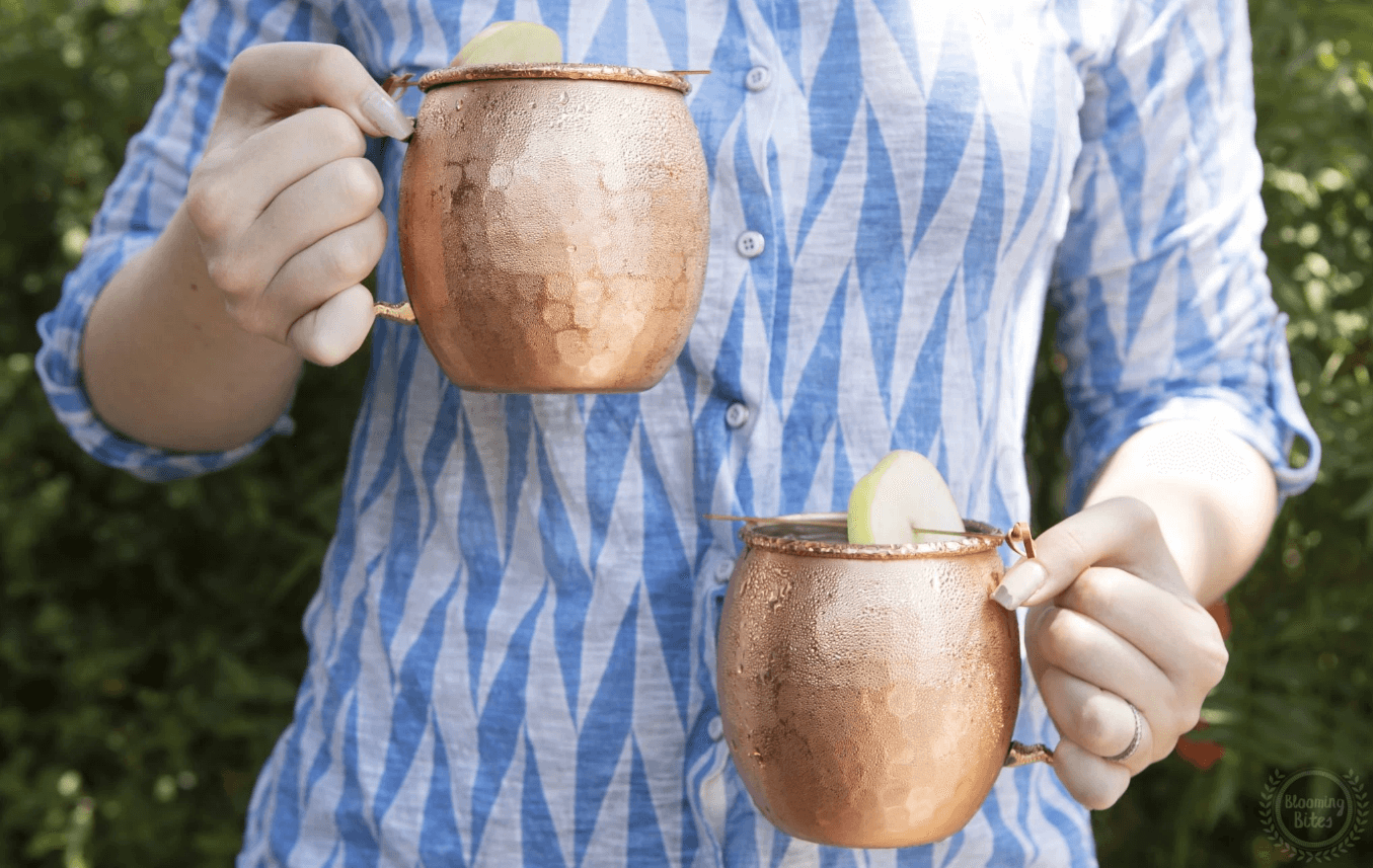 person wearing blue clothes carrying two Moscow Muled copper mugs in each hand