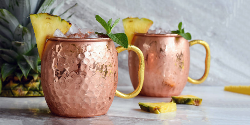 two Moscow Muled copper mugs filled with ice and pineapple and mint leaves wedged on the rim