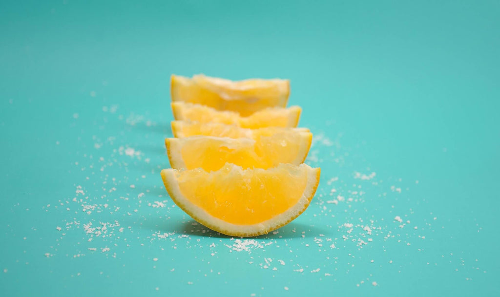 four slices of lemon lined up and sprinkled with salts