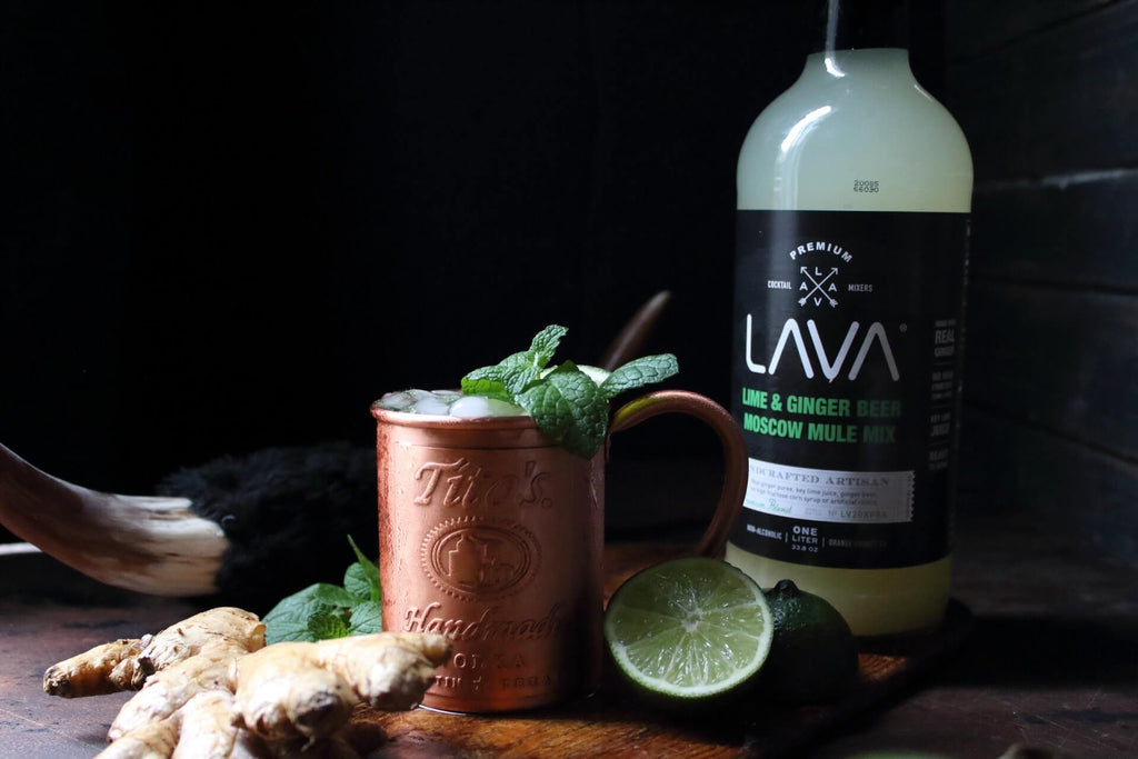 copper cup filled with crushed ice and mint leaves beside pieces of ginger and sliced lime