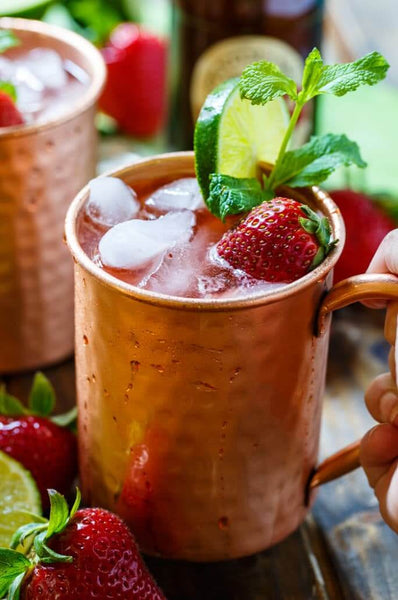 two copper mugs filled with liquid ice strawberry sliced citrus and herb