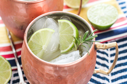 Moscow Muled copper mug filled with liquid ice cubes lime slice and sprig of herb