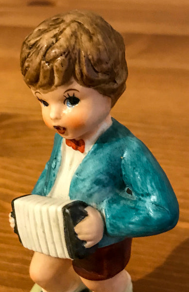 Figurine of young boy playing concertina - TheReedLounge.com