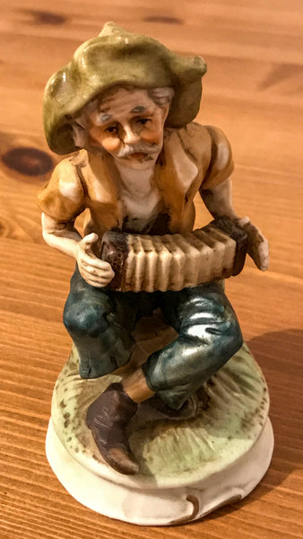 Pottery figurine of an Elderly gentleman playing concertina outside.