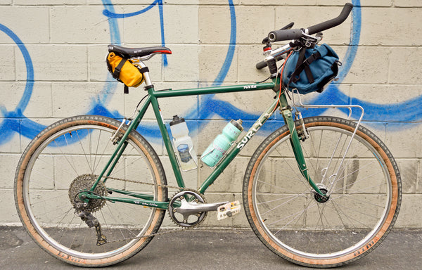 Here we have a Surly Pack Rat with a Drafter on the saddle and a Jammer Handlebar bag made by Road Runner Bags with Velo Orange Crazy Bars