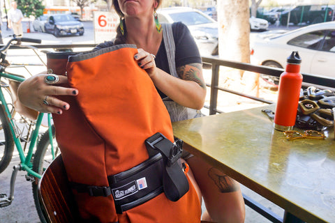 Road Runner Bags Medium Roll Top Pro in Rust being cycling by bike around los angeles city by a commuter