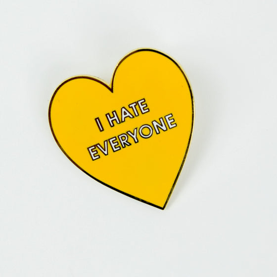 Chez Gagne I Hate Everyone Hard Enamel Heart Pin. This hilarious and relatable enamel pin is mounted to a pink and foil patterned Card Backer. The perfect enamel pin for COVID. Ideal for your denim jacket, face mask or backpack!