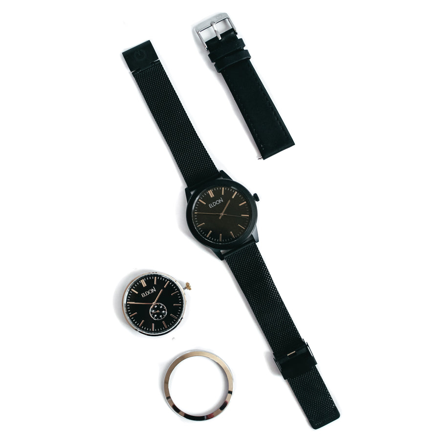 Black and silver watch with a black mesh strap, black face and black bezel