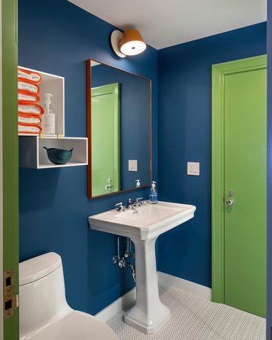 A green bathroom door stands out against this blue wall to help patients find where they are going.