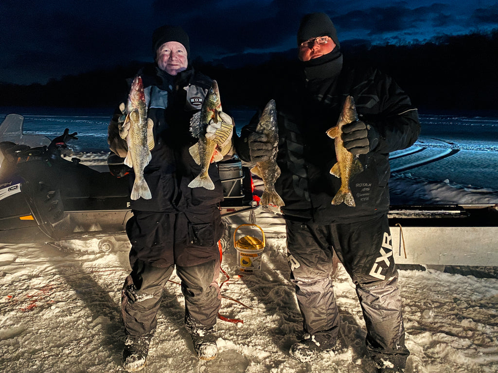 Ice fishermen at night holding their catch Ontario