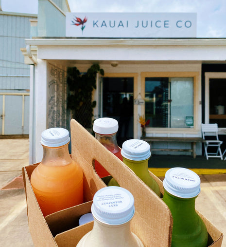 A box of juices in front of a Kauai Juice storefront