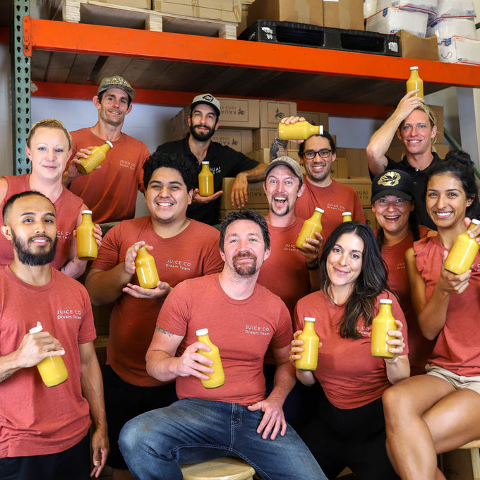 Back of house team members holding bottles of juice