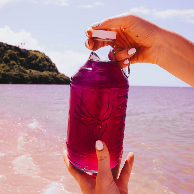 Hands holding bottle of kombucha on the beach