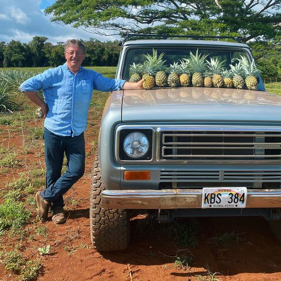 Farmer standing next to truck with pineapples on the hood