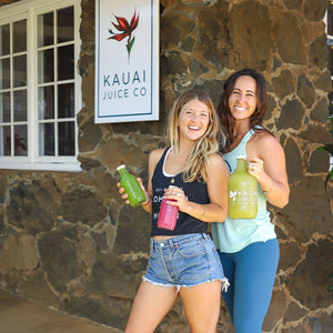 Two staff members holding bottles of juice in front of Kauai Juice store