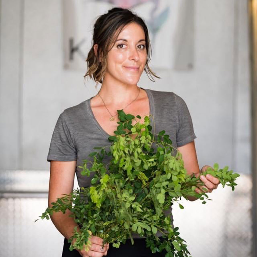 Kristal Muhich holding fresh leafy vegetables