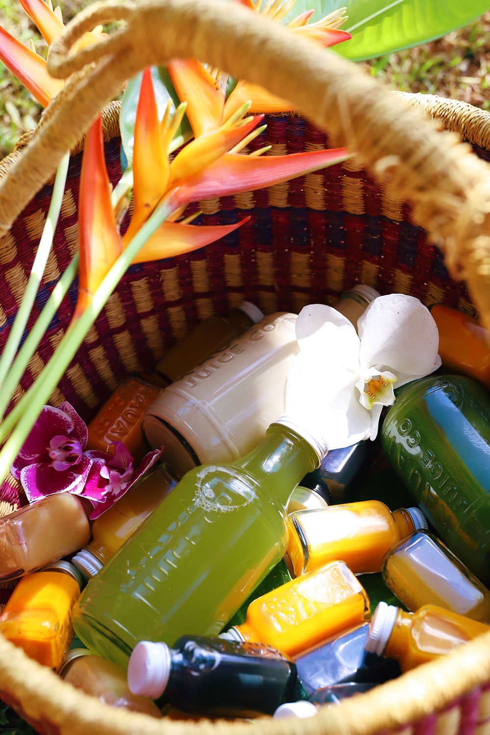 Bottles of elixers, kombucha, and juice in a basket