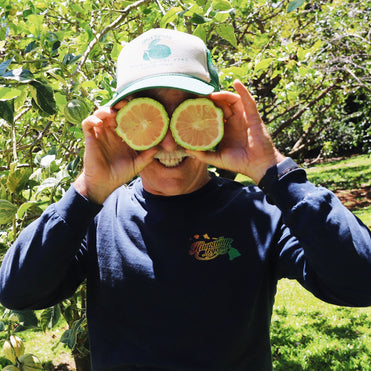 Farmer holding lemons up to his eyes