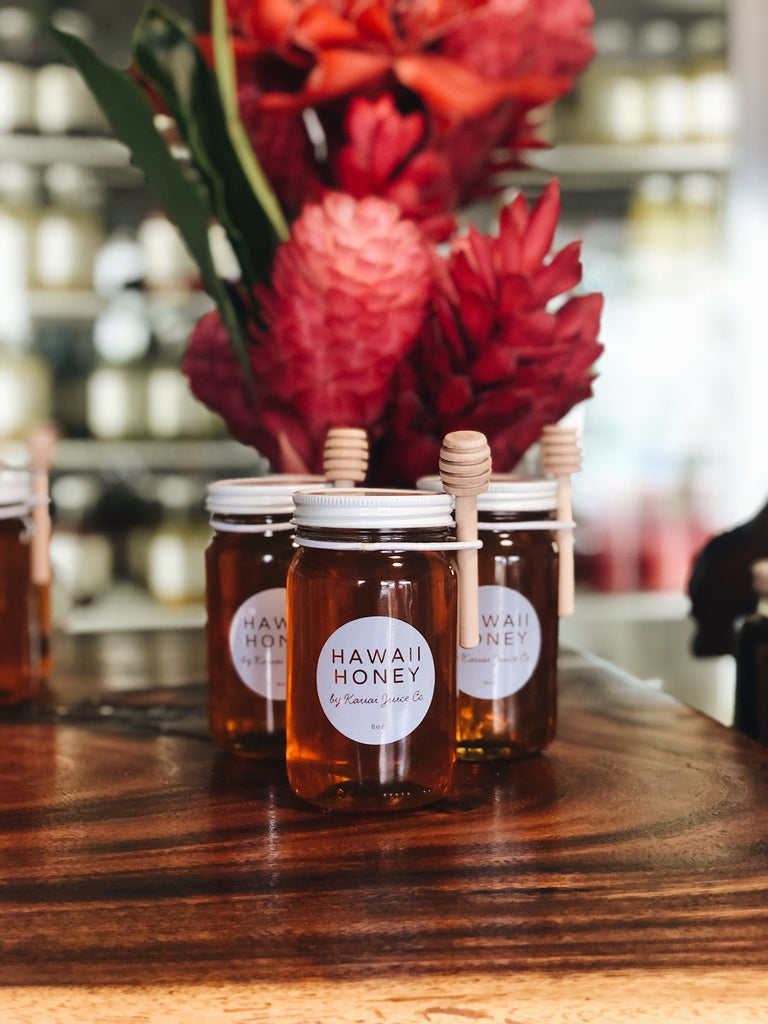 three jars of Hawaii Honey with tropical flowers