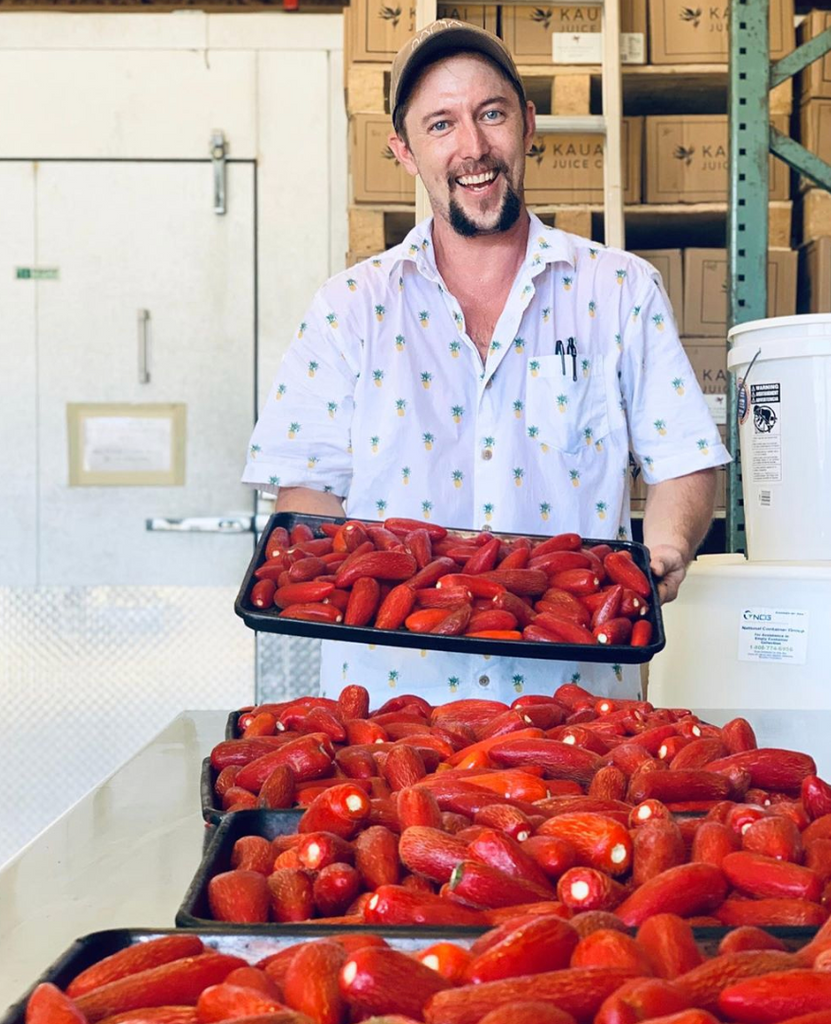 man with chili peppers on trays