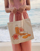 woman on beach holding tote back with drawing of Kauai Juice Co bottles and hibiscus flowers