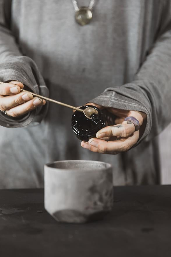 person scooping black jar of resin using small spoon