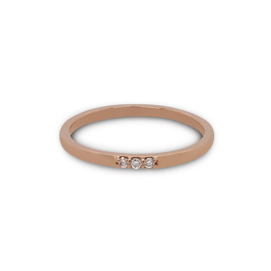 Front view of 3 diamond stacking band cast in 14 kt rose gold.