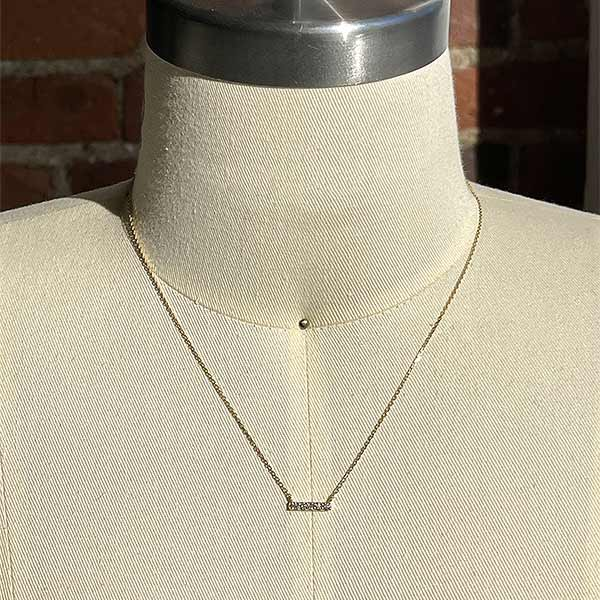 Load image into Gallery viewer, A solid 14 kt yellow gold bar necklace with 5 round cut diamonds on a body form for scale.