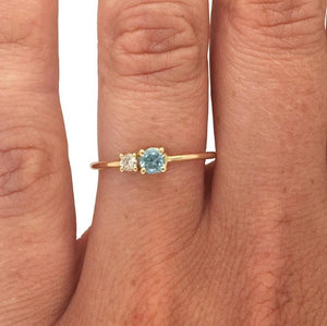 Load image into Gallery viewer, Round cut blue zircon and diamond ring cast in 14 kt yellow gold on left ring finger.