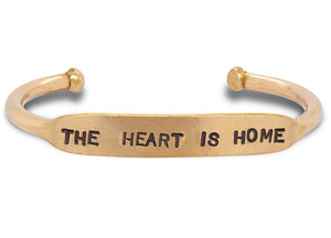 "Load image into Gallery viewer, Hand stamped, solid brass cuff that says ""the heart is home."""