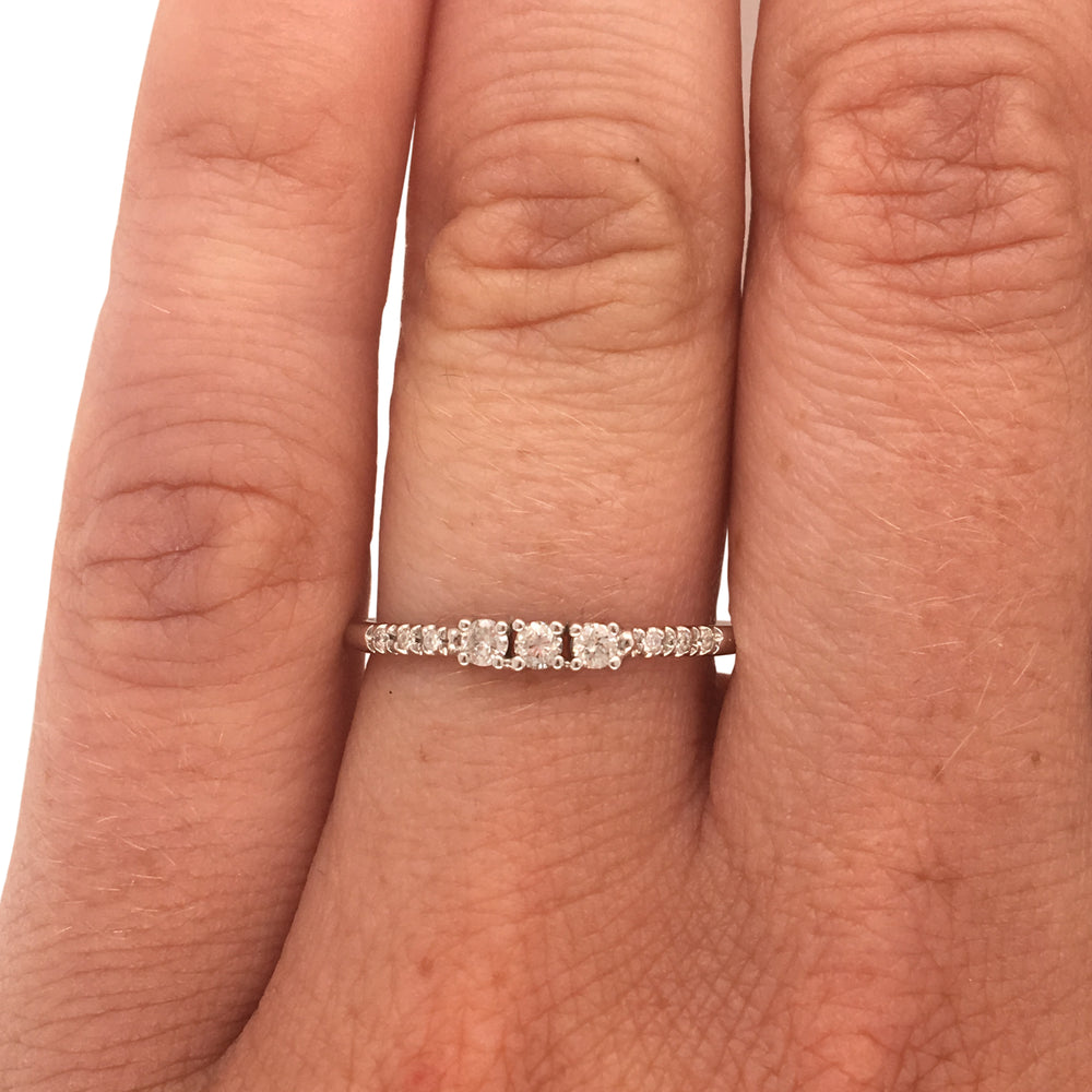 Load image into Gallery viewer, A diamond ring with 3 center round cut diamonds flanked by 6 round cut pavé set diamonds cast in 14 kt white gold on wearer's left ring finger for scale.