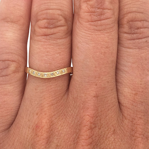 Princess cut diamond shadow band set in 14 kt yellow gold on left ring finger.