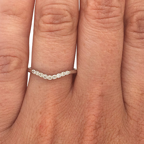 Shadow band with 9 round cut diamonds set in 14 kt white gold on left ring finger.