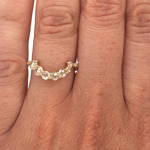 Asymmetrical, rose cut diamond shadow band with 7 rose cut diamonds and 10 round cut diamonds set in 14 kt yellow gold on left ring finger for scale.