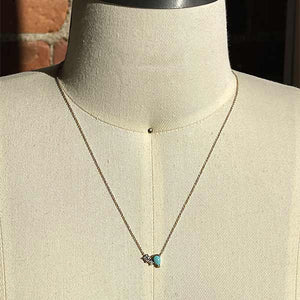 Load image into Gallery viewer, A necklace featuring two round cut diamonds set to one side of a pear cut turquoise stone set in 14 kt yellow gold on a body form.