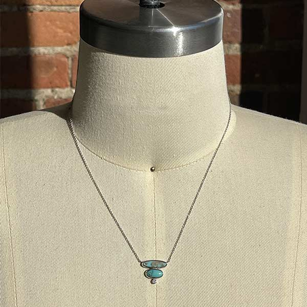 Load image into Gallery viewer, Double oval cut turquoise and 1 round cut diamond necklace set in 14 kt white gold on a body form.