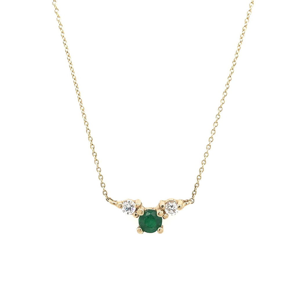Front view of a round cut double diamond and round cut emerald pendant necklace cast in 14 kt yellow gold.