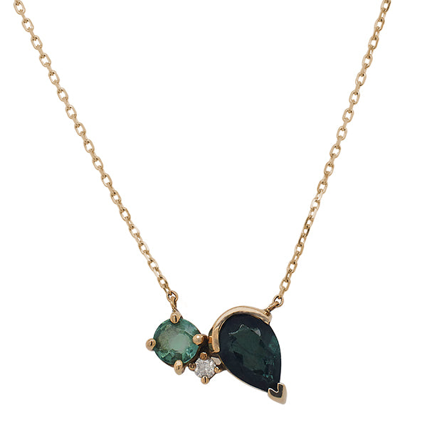 Asymmetricall necklace with a light green, round cut tourmaline, round cut diamond, and dark green, pear cut tourmaline set in 14 kt yellow gold.