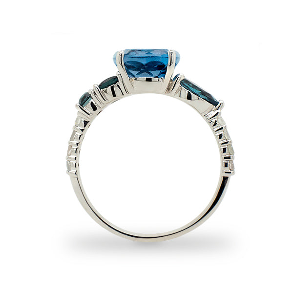 Load image into Gallery viewer, Side view of cushion cut, London blue topaz with 2 round and 1 pear cut green tourmaline stones, and 8 round cut diamonds going down the band cast in 14 kt white gold.