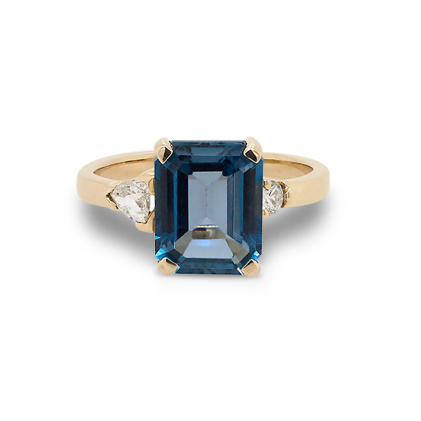 Front view of emerald cut London blue topaz and round and trillion cut diamond ring cast in 14 kt yellow gold.