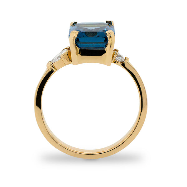 Side view of emerald cut London blue topaz and round and trillion cut diamond ring cast in 14 kt yellow gold.