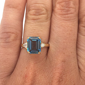 Load image into Gallery viewer, Emerald cut London blue topaz and round and trillion cut diamond ring cast in 14 kt yellow gold on left ring finger.