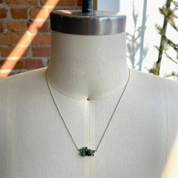 Malachite and emerald cluster necklace in a 14 kt yellow gold setting on a body form for scale.