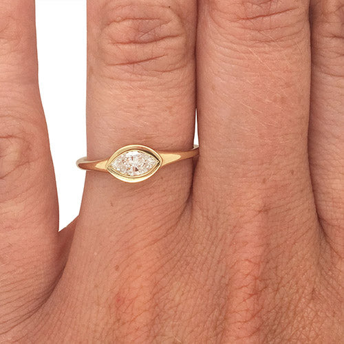Bezel set, marquise cut diamond ring set in 14 kt yellow gold on left ring finger.