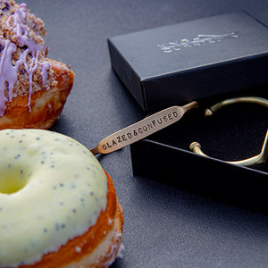Load image into Gallery viewer, Two brass cuffs and donuts from the  King + Curated and NoFoDoCo collaboration .