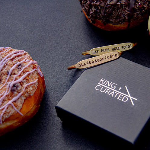 Two brass cuffs and donuts from the  King + Curated and NoFoDoCo collaboration.