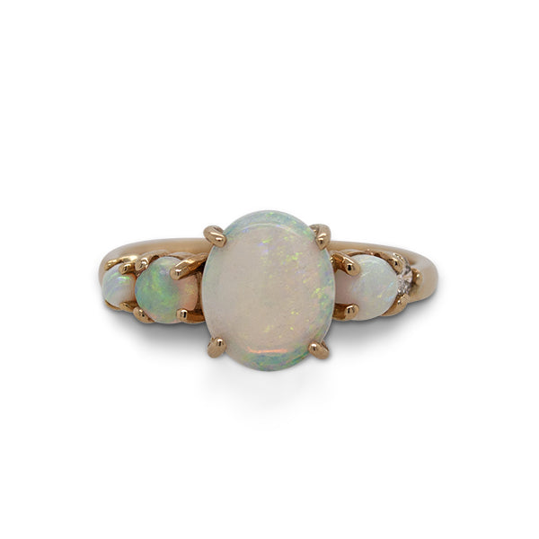 Front view of an asymmetrical opal and diamond ring cast in 14 kt yellow gold.