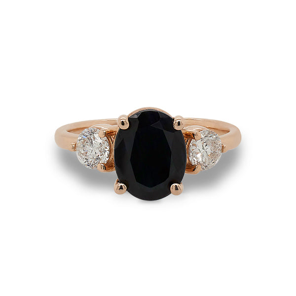 Front view of oval cut black sapphire and round cut diamond ring set in 14 kt rose gold.